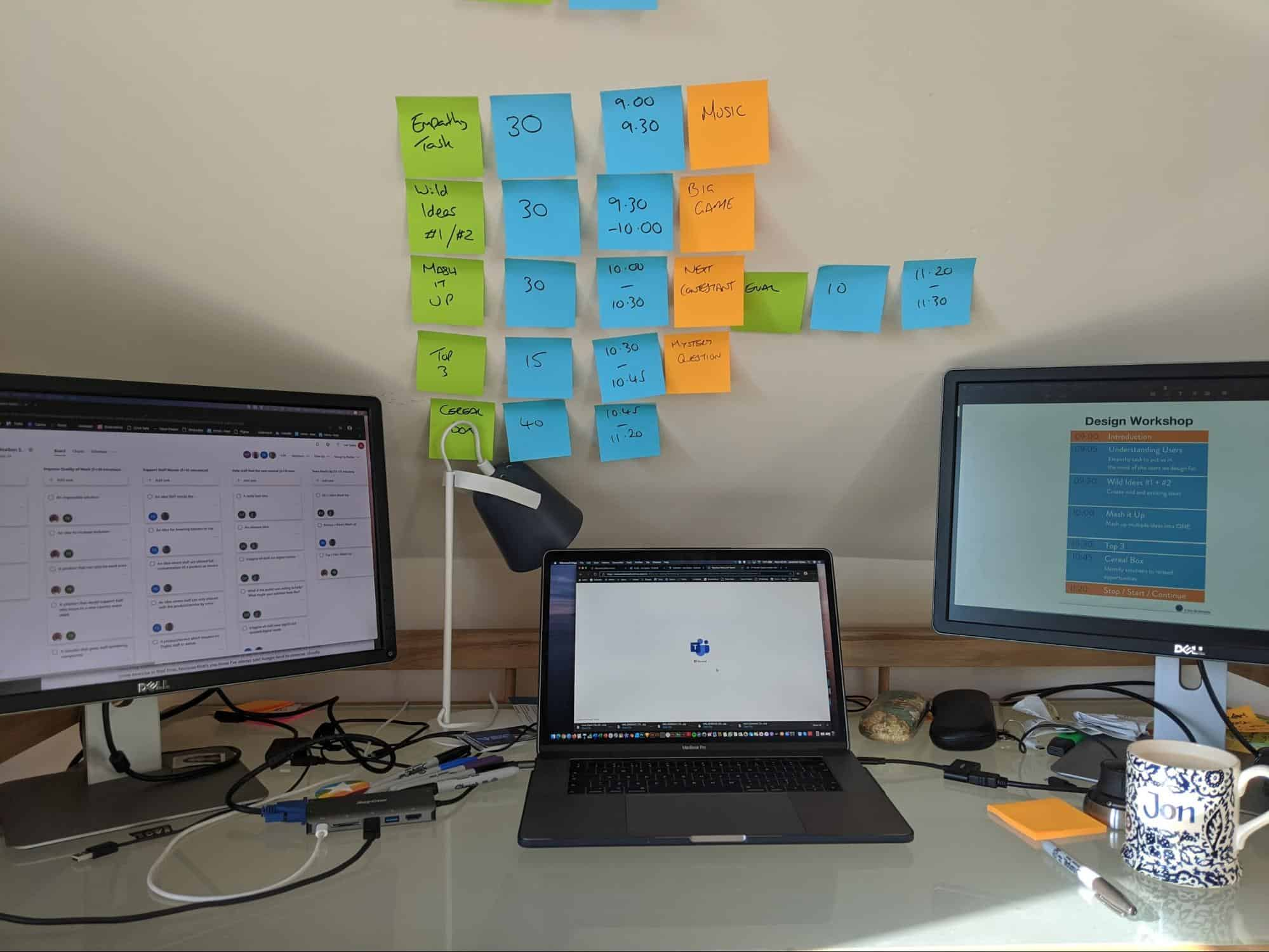 Three computers on a desk with post-it notes on the wall
