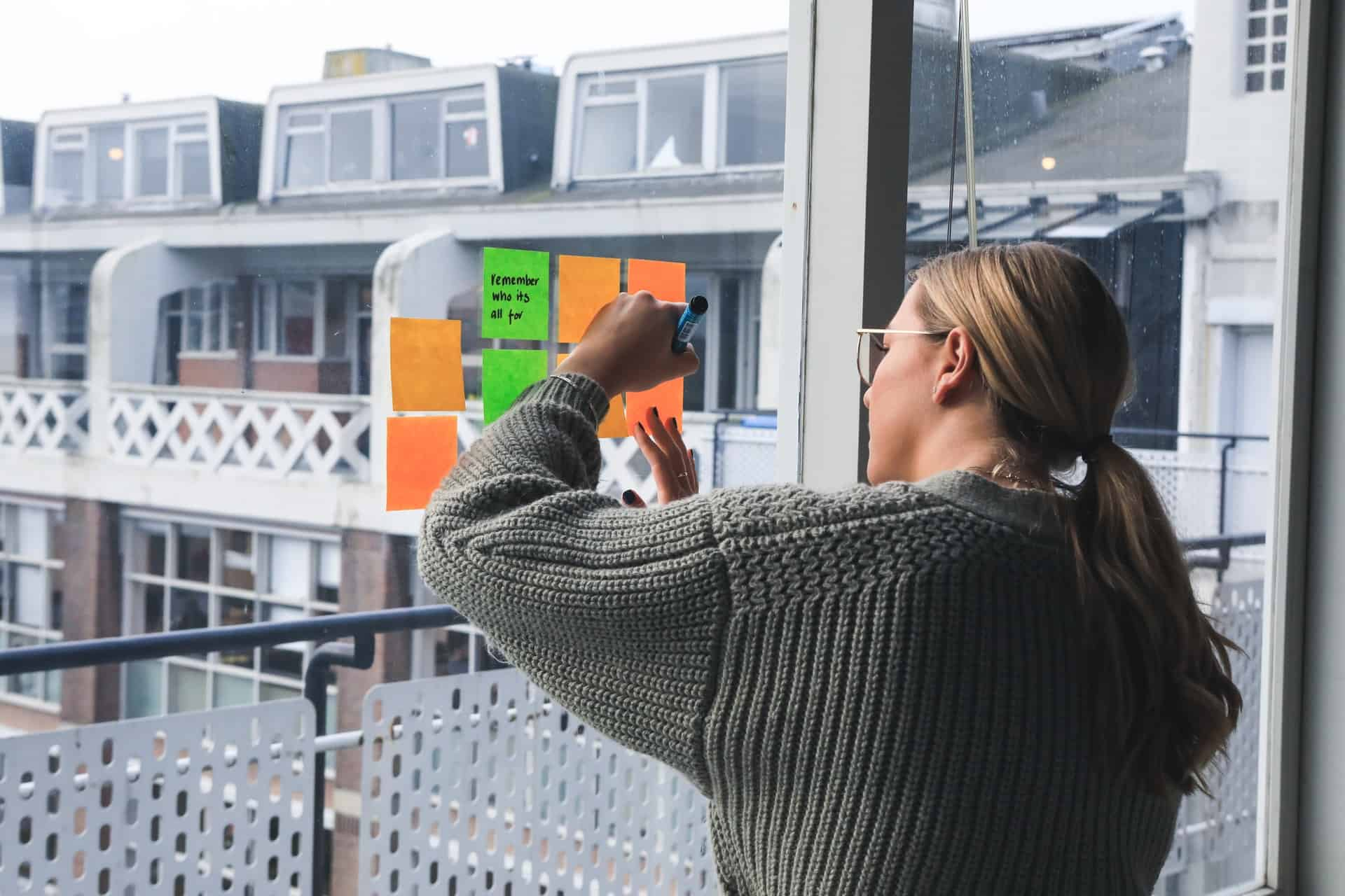 A woman writing on a colourful sticky note against a glass wall